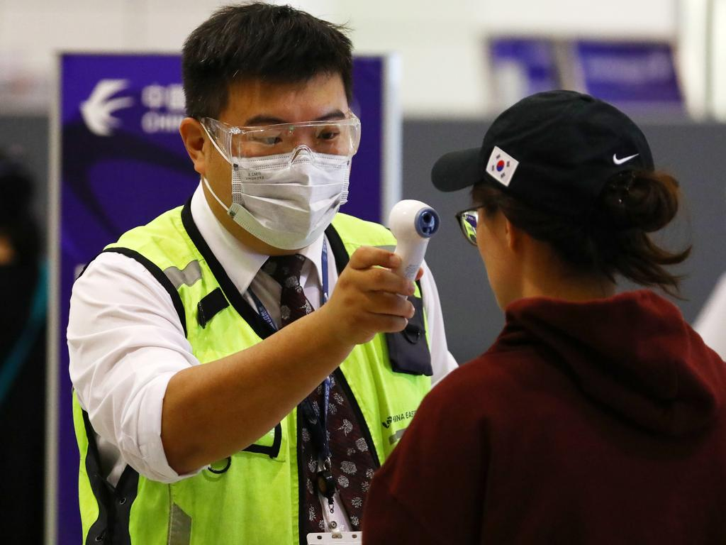 Passengers arriving and departing from Sydney International Airport take precautions by wearing a variety of masks. Image: Matrix