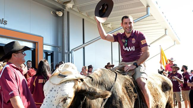 Cameron Smith poses for a photo on a bull during s Maroons visit to Longreach.