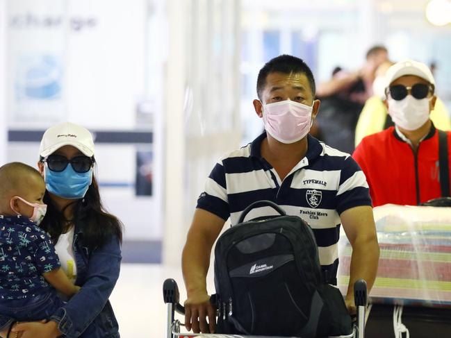 Passengers arriving and departing at Sydney International Airport take precautions by donning a variety of face masks. Picture: Matrix