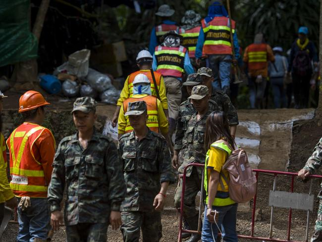 Thai soldiers and volunteers are seen at the entrance of Tham Luang cave.
