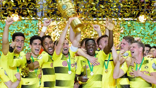Dortmund's French midfielder Ousmane Dembele (C) and teammates celebrate with the trophy after winning the German Cup (DFB Pokal).