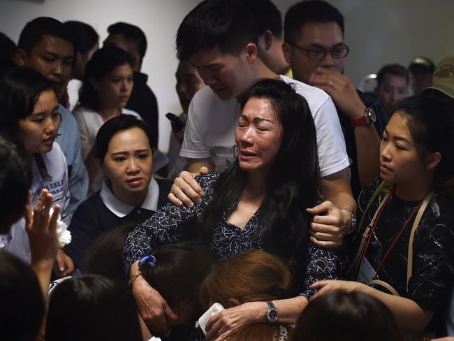 Family members of passengers react after watching news reports showing an unidentified body floating in the Java Sea. Picture: Manan Vatsyayana