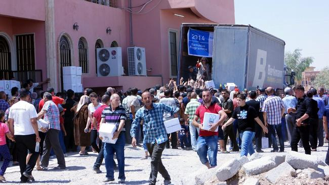 Displaced Iraqi Christians who fled with families from Mosul city receives humanitarian aid at Virgin Mary church in Qaraqosh village near Mosul city, northern Iraq on 20 July 2014. EPA/MOHAMMED AL-MOSULI