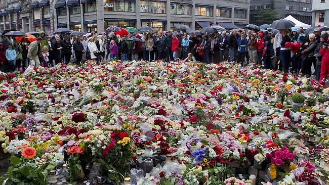 People stand by flowers and candles left on July 24, 2011 in Oslo in memory the victims of a bomb explosion which ripped through government buildings and the shooting spree at the youth camp of the Norwegian Labour Party. Picture: Roald Berit / AFP