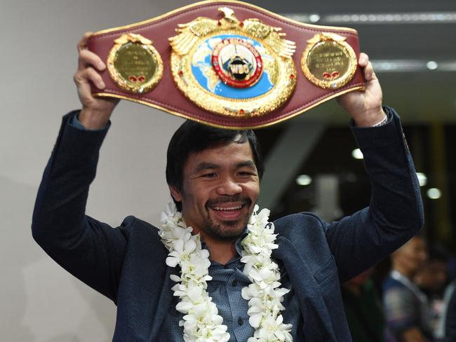 Manny Pacquiao holds up his WBO welterweight title belt.