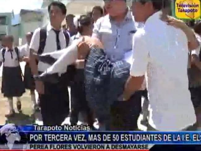 Staff carry a 'possessed' student from Elsa Perea Flores School