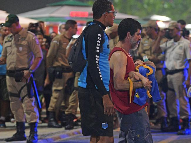 An injured man carries his baby at the scene of the car crash. Picture: AFP / CARL DE SOUZA
