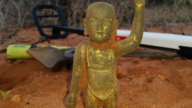 The discoverers found a lot of beer cans before their metal detector (background) unearthed the baby Buddha.