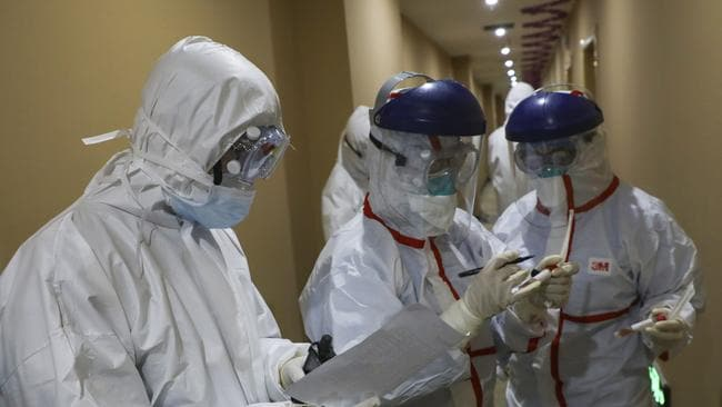 A medical worker in a protective suit collects a sample for testing from a suspected virus patient at a hotel in Wuhan. Picture: Chinatopix via AP
