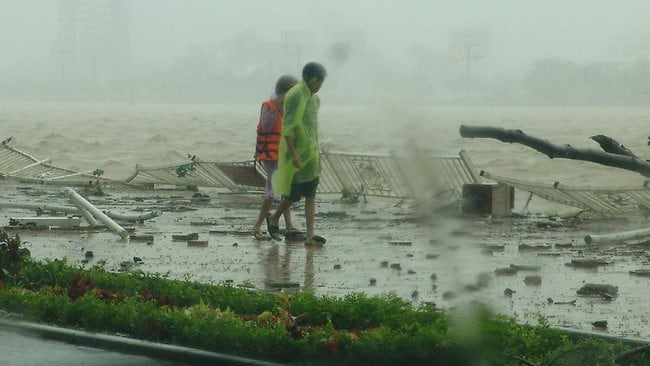 People walk along the Han river as Typhoon Nari hits the central coastal city of Da Nang in Vietnam.