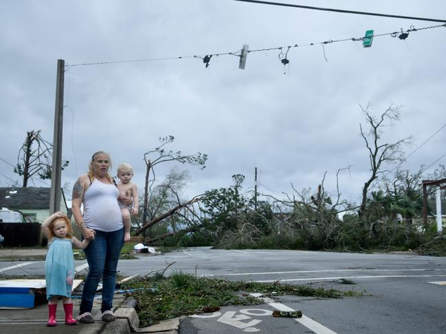 A woman and her children wain near a destroyed gas station after Hurricane Michael in Panama City, Florida. Picture: AFP
