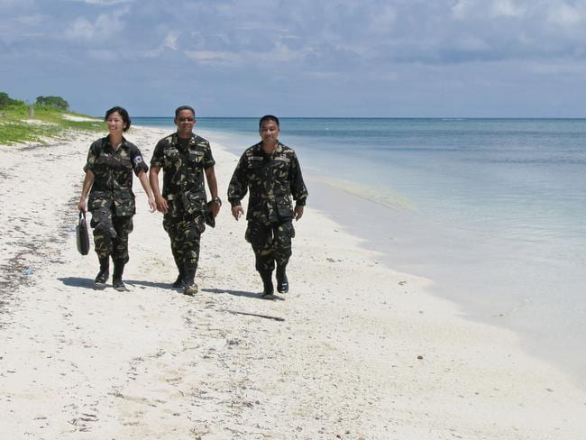 Philippine Army troops take a leisurely walk along the white sand beach of Thitu (Pag-asa). Picture: AP