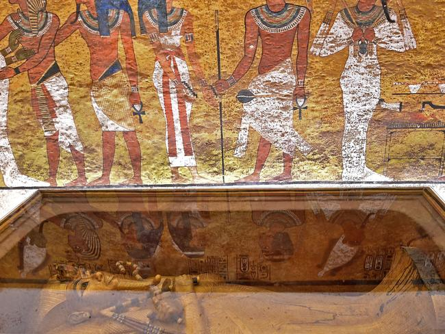 The golden sarcophagus of Tutankhamun and part of the murals painted on the walls of his tomb. Picture: AFP