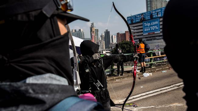 A protester uses a bow and arrow while standing on a barricaded street outside The Hong Kong Polytechnic University. Picture: ISAAC LAWRENCE / AFP.
