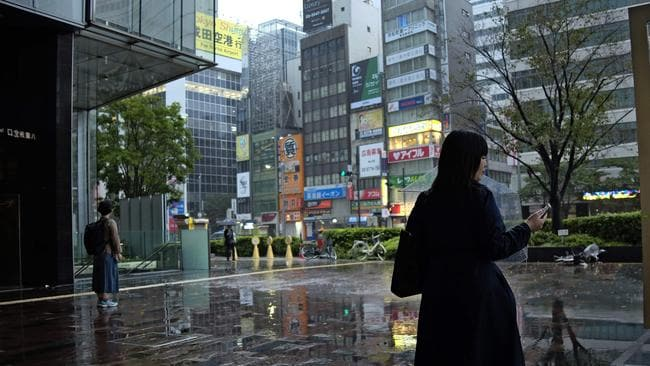 Silent streets: commuters watch the rain at an entrance of the JR Tokyo Station. Picture: AFP