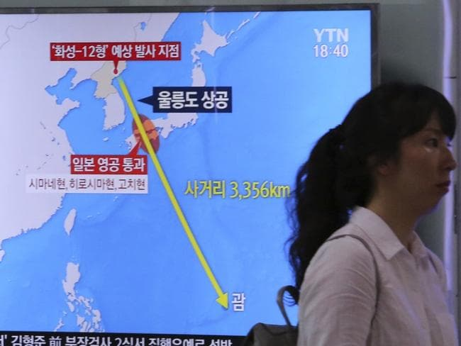 A woman passes by a TV screen showing a local news program reporting on North Korea's threats to strike Guam with missiles. China has also been showing increase military interest in the US naval and air force facilities based there. Picture: AP /Ahn Young-Joon