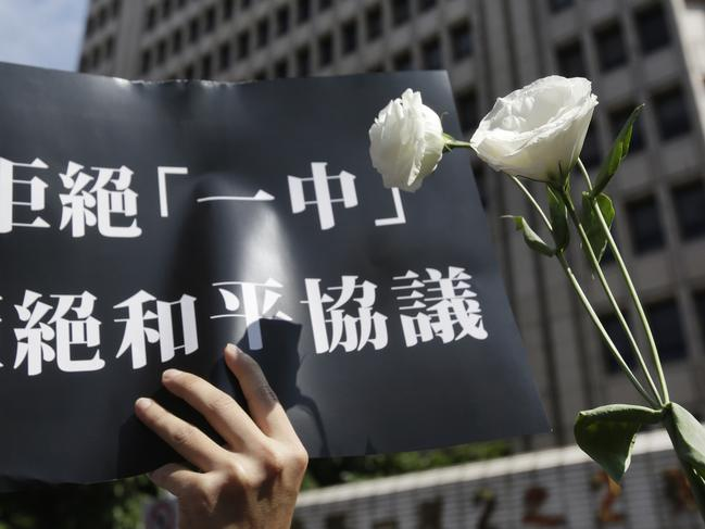 "A supporter holds a slogan reading ""Refuse One China. Refuse Peace Agreement"" with a white flower to oppose the extradition law. Picture: Chiang Ying-ying/AP"