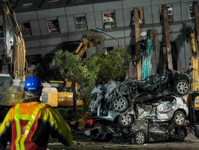 A rescue worker (front left) walks towards a stack of cars that were crushed when a building (collapsed in the earthquake.