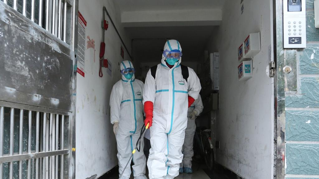 Medical staff wearing protective clothing disinfect a residential area in Ruichang, part of Jiujiang in China's central Jiangxi province next to Hubei province. Picture: STR/AFP