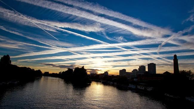 Airplane Contrails: Globalised transportation networks, especially commercial aviation, are a major contributor of air pollution and greenhouse gas emissions. Photo of contrails in the west London sky over the River Thames, London, England. Pic: Ian Wylie.