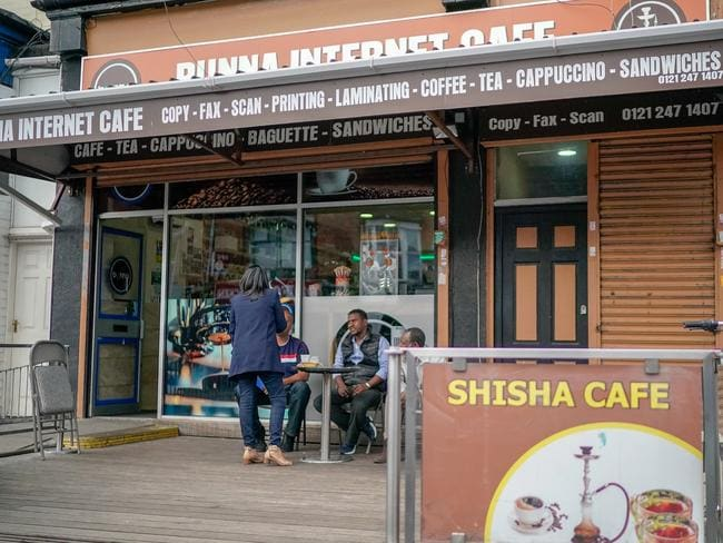 Customers sit outside the Bunna internet Cafe in Stratford Road in Sparkbrook, which has been searched by police as part of the investigation into the suspected terror attack in Westminster. Picture: Getty