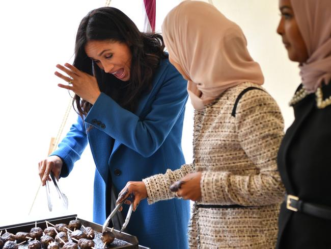 Meghan, Duchess of Sussex helps to prepare food at the launch of a cookbook with recipes from a group of women affected by the Grenfell Tower fire. Picture: AFP
