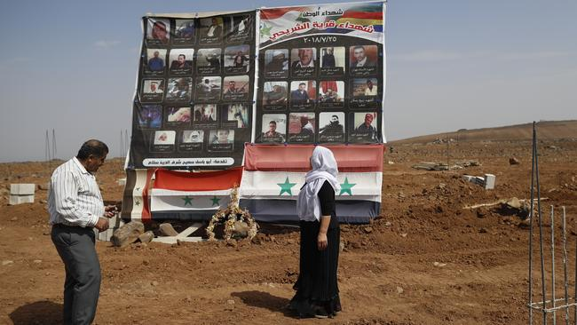 A Druze family visits a memorial erected in honor of the 37 Druze who killed during a stunning Islamic State attack at the village of Shreihi in the southern province of Sweida, Syria. Picture: / Hassan Ammar.