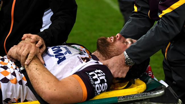 Andrew McCullough of the Brisbane Broncos is taken off the field injured.