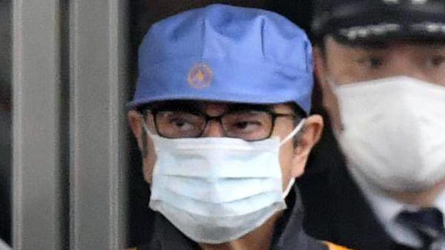 In this March 6, 2019, file photo, a masked man, front with blue cap, believed to be former Nissan Chairman Carlos Ghosn, leaves Tokyo's Detention Centre. Picture: Yu Nakajima, Kyodo News
