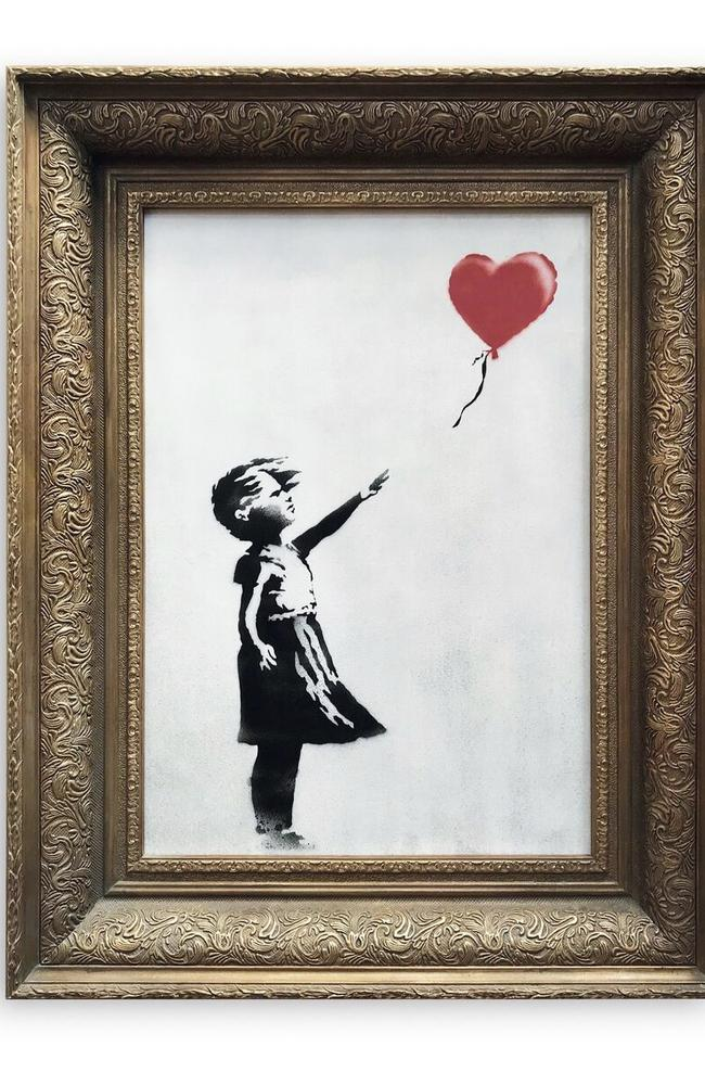 Banksy's Girl with Balloon, pictured before the auction, has been renamed Love Is In The Bin. Picture: Sotheby's/via AP