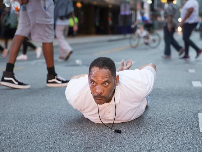 """A man lays on the ground after yelling """"Don't shoot me"""" at police during a rally in Dallas. Picture: AFP"""