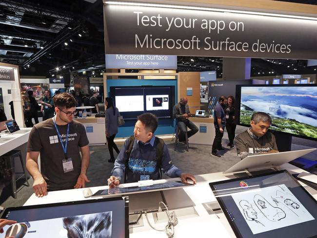 Workers demonstrate Microsoft Surface devices during the opening day of the Microsoft Build 2017 developers conference in Seattle. Picture: Elaine Thompson
