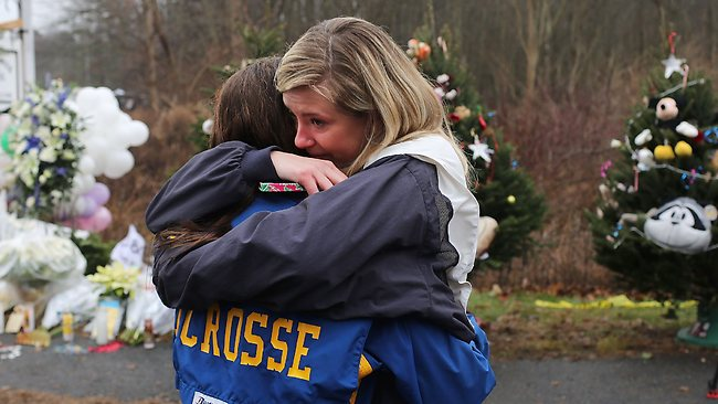 Kristen Brassard (Left) and Kat Donohue, both of Newtown, hug outside of the Sandy Hook School as they try to come to terms with the tragedy. Picture: AFP