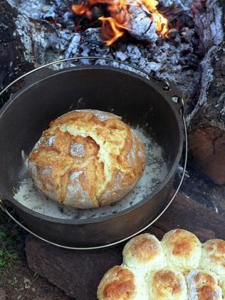 FScones (bottom) and damper bread cooked in a camp oven on hot coals.