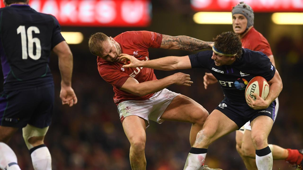 Scotland's Hamish Watson fends off Ross Moriarty of Wales at the Principality Stadium.