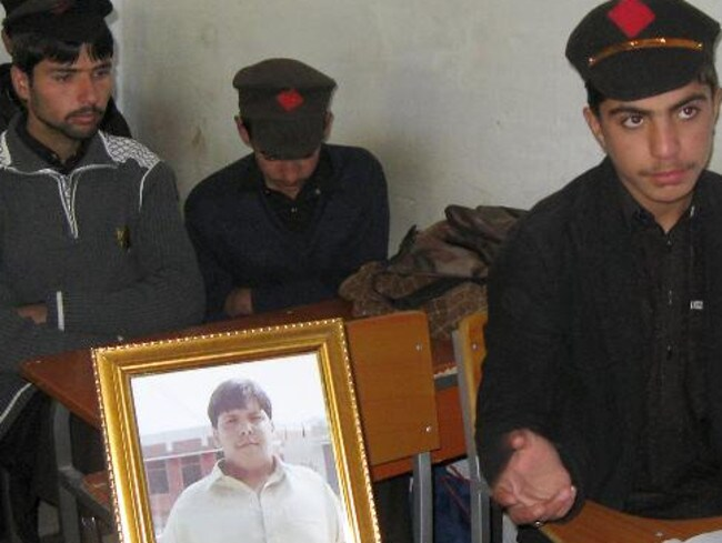 Classmates sit next to a portrait of Aitzaz at school today as they mourn their peers massacred by the Taliban overnight.
