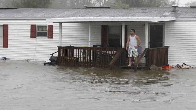 Jarod Wilton looks at the flood waters rising to his doorstep in Alliance, North Caroline. Picture: AP