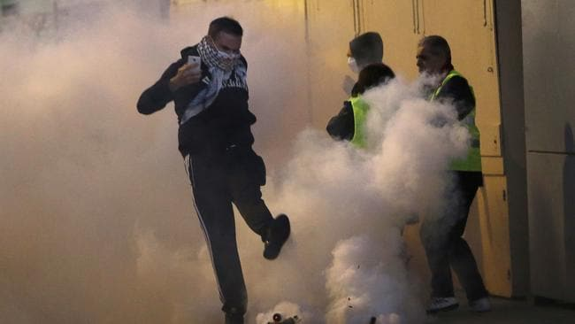 A demonstrator kicks a teargas canister away during clashes with police in Marseille. Picture: AP