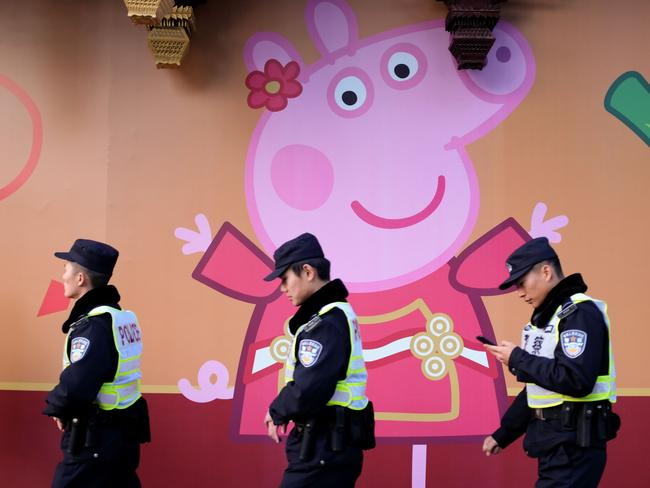 Reprieve … This picture taken on January 25, 2019 shows police walking past a Peppa Pig figure on a wall in Shanghai. Picture: AFP
