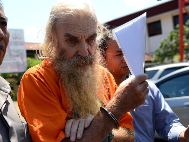 Robert Andrew Fiddes Ellis is escorted from his holding cell to a police car. Picture: Nashyo Hansel