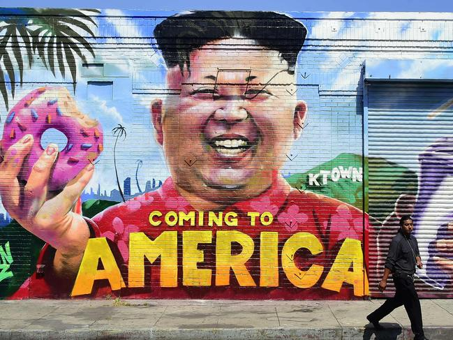 A pedestrian walks past a mural titled 'Coming To America' depicting North Korean leader Kim Jong-un by graffiti artsists @welinoo, @balstroem and @sorenarildsen in Los Angeles, California. Picture: AFP