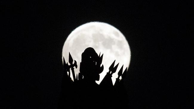"""A statue on the roof of the Portuguese finance ministry in Lisbon is silhouetted against a so-called """"supermoon"""" full moon Saturday.(AP Photo/Armando Franca)"""