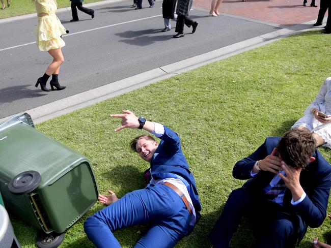 Too late — the wheelie bin comes crashing to the ground as the man celebrates and his friend despairs. Picture: Tracey Nearmy/AAP Image