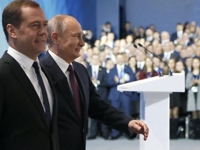 Russian President Vladimir Putin (R) and Prime Minister Dmitry Medvedev walk together as they attend the United Russia Party's 17th convention in Moscow. Picture: AFP