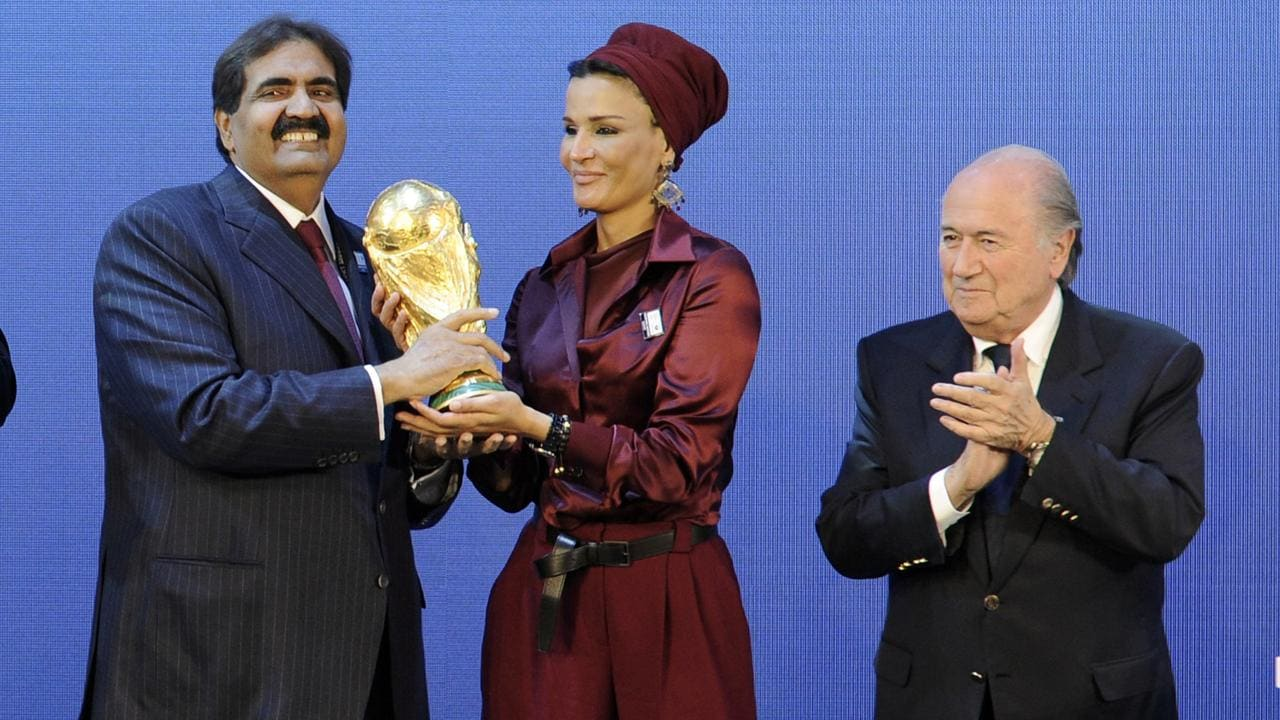 Emir of the State of Qatar Sheikh Hamad bin Khalifa Al-Thani (R) and his wife Sheikha Moza bint Nasser Al-Missned (C) receive the World Cup trophy from FIFA President Joseph Blatter in 2010. Photo: Sebastien Derungs/AFP.