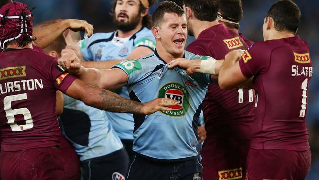 Greg Bird Blues wrestles with Maroons players during game two.