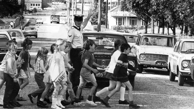 A police officer helps children cross the road in 1972.