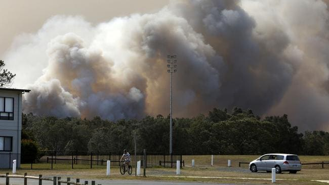 A bushfire burns out-of-control near houses at Old Bar, NSW. Picture: AAP/Darren Pateman