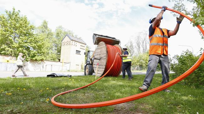 Workers unspool high-speed internet cable.