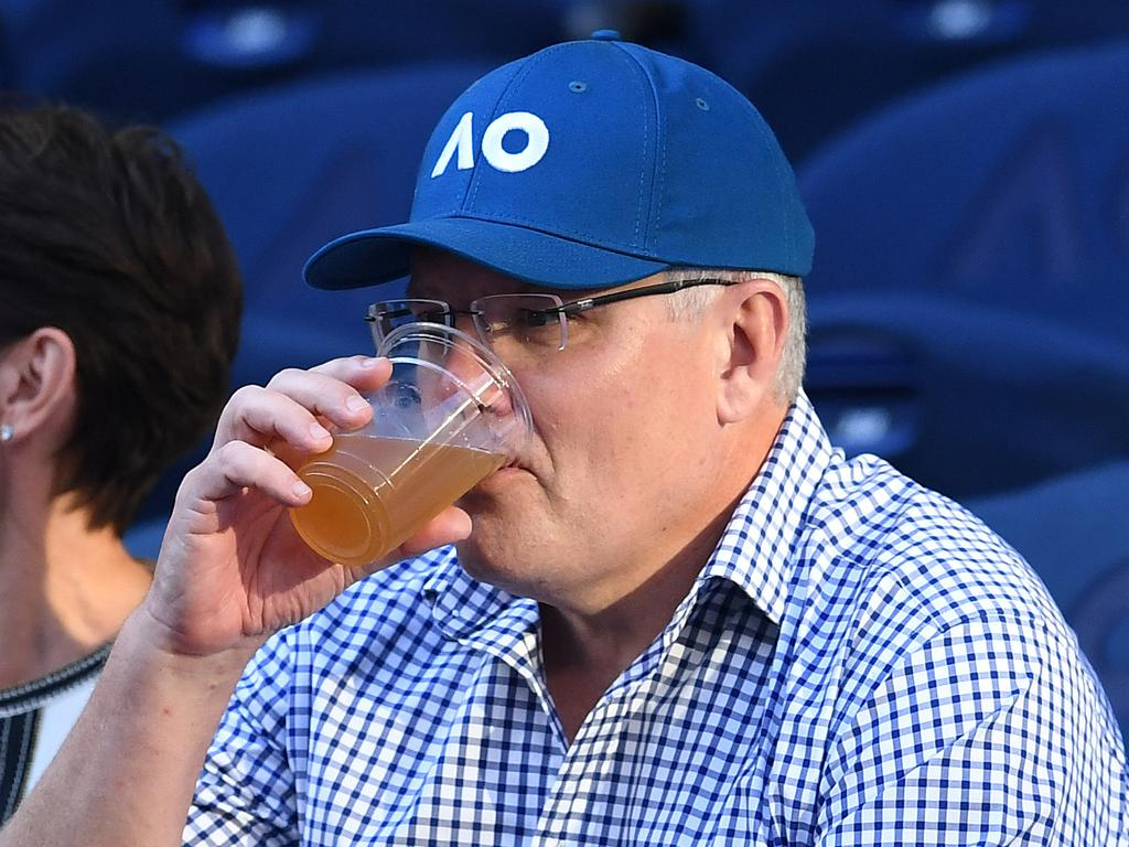 Australian Prime Minister Scott Morrison drinks a beer during the match between Roger Federer of Switzerland and Stefanos Tsitsipas of Greece on day seven of the Australian Open tennis tournament in Melbourne, Sunday, January 20, 2019. (AAP Image/Lukas Coch) NO ARCHIVING, EDITORIAL USE ONLY